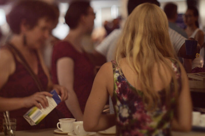 Blonde Frau mit dem Rücken zur Kamera bereitet Kaffee auf einem Tresen in einem überfüllten, belebten Raum zu