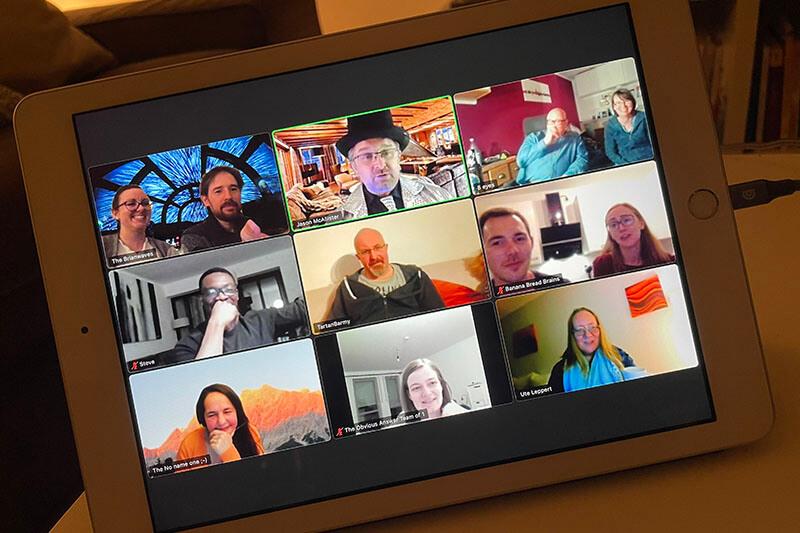 iPad auf dem Tisch zeigt Zoom-Anruf mit neun Teilnehmern