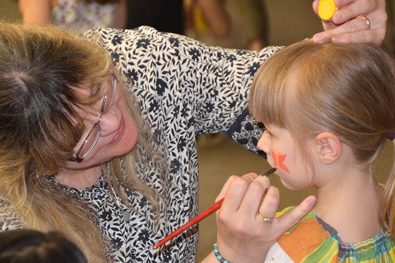 Frau malt Schmetterling auf die Wange eines jungen Mädchens