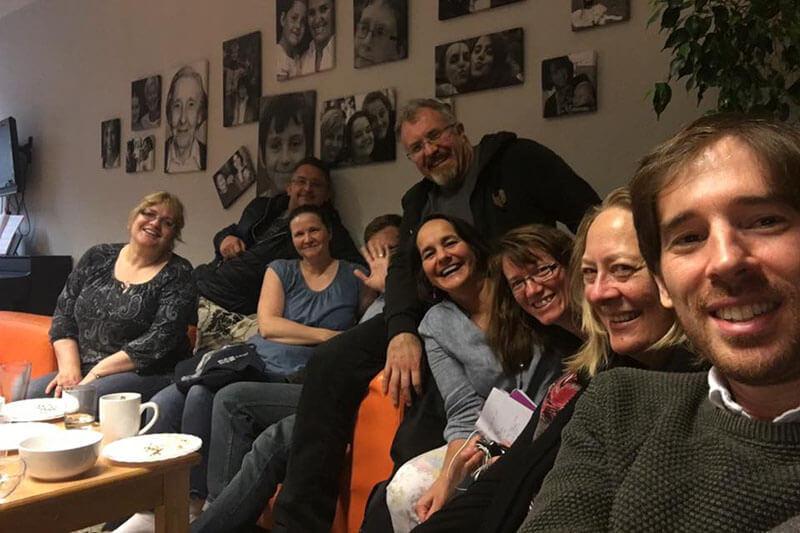 Selfie einer Gruppe von neun Erwachsenen, die lächelnd und winkend auf Sofas sitzen