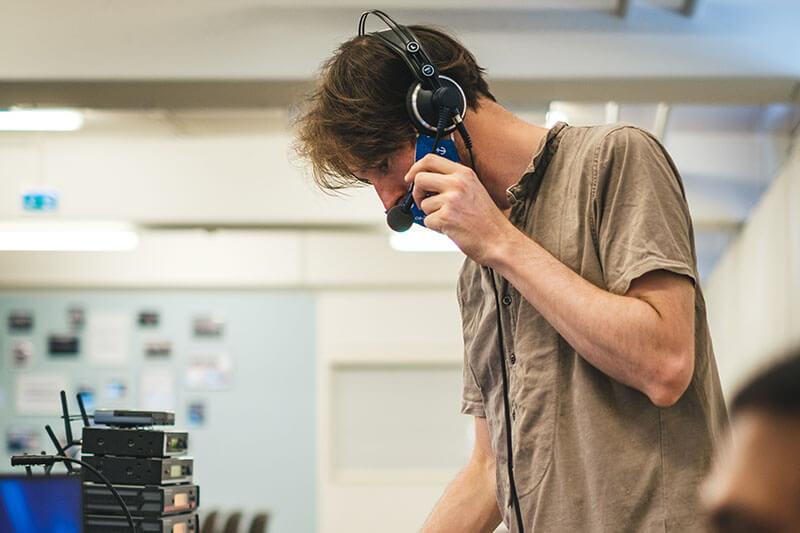 Weißer Mann mit Headset führt Soundcheck durch