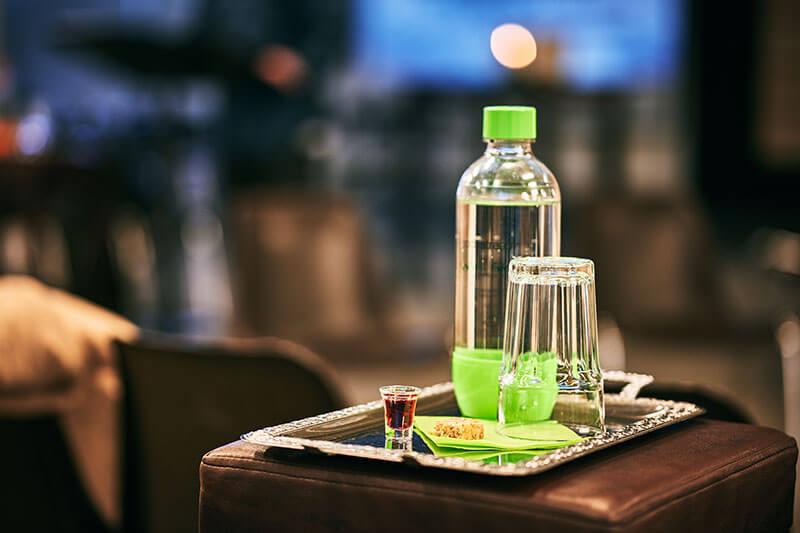 Wasserflasche und Glas auf einem Silbertablett mit kleinem Weinbecher und Brot für das Abendmahl