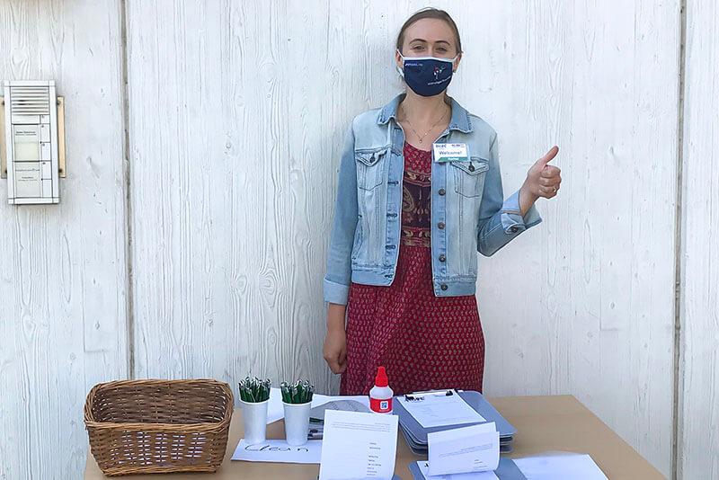 Junge europäische Frau mit Maske steht an einem Check-in-Tisch mit Daumen nach oben