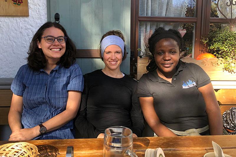 Drei Frauen, die draußen im Sonnenlicht an einem Holztisch sitzen, mit dem Rücken gegen Haustür und Fenster