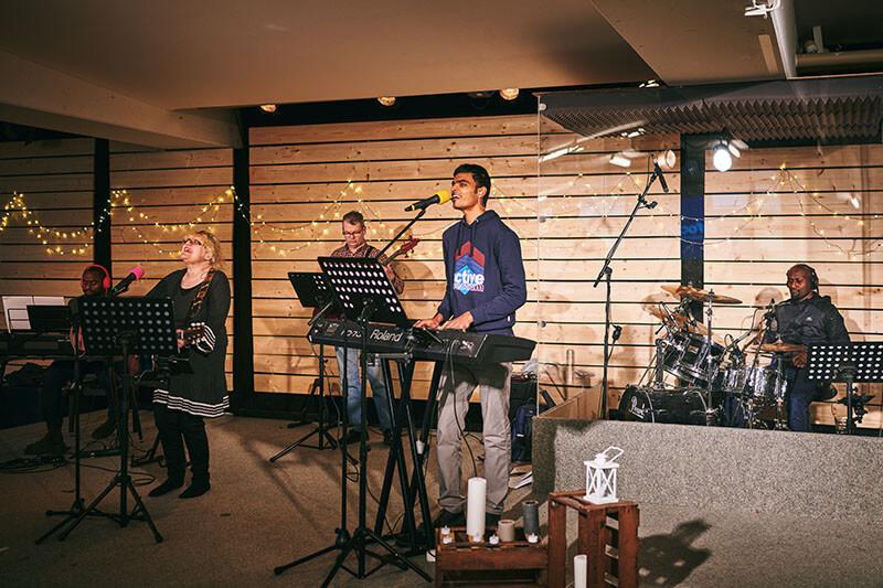 Fünf Musiker verschiedener Nationalitäten spielen auf der Bühne mit Lichterketten
