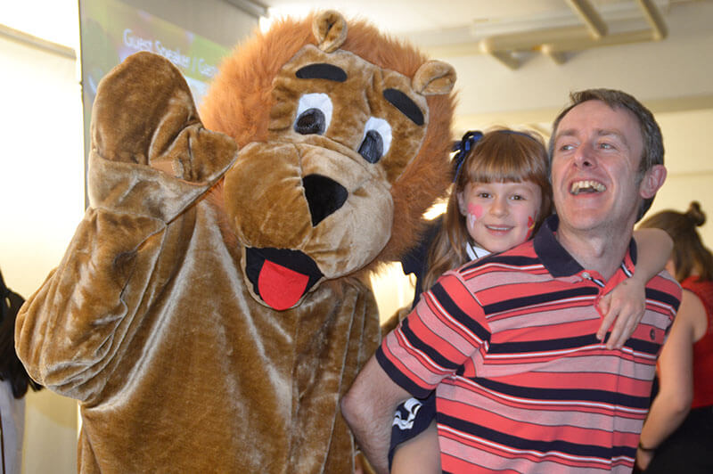Person in lion mascot costume waving next to a smiling father carrying smiling daughter on his back