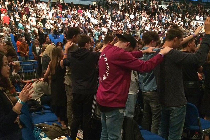 Crowded stadium of youth pray and worship together