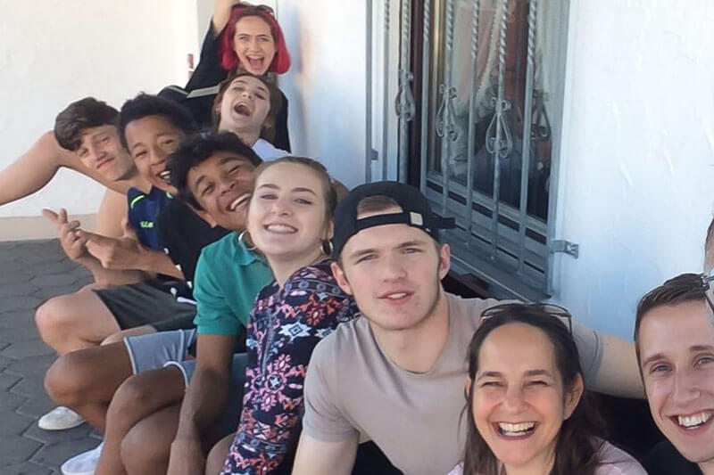 Group of nine youth of different nationalities sitting in an uneven row, excited and smiling